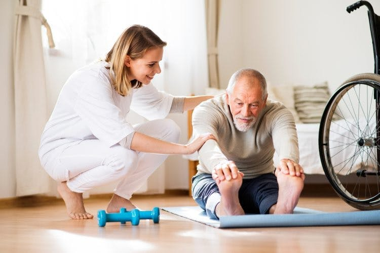 physiotherapist helping patient with stretching passive and active exercises