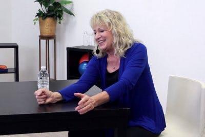 ot demonstrating tabletop shoulder exercises for stroke patients