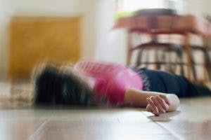 woman lying on the floor experiencing a seizure after TBI