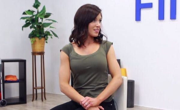 physical therapist demonstrating seated core exercises for stroke patients