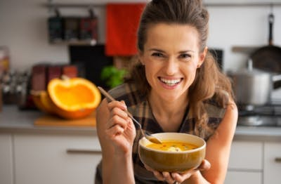 woman leaning on counter smiling, holding bowl of food you can eat with dysphagia