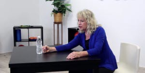 therapist punching water bottle for occupational therapy