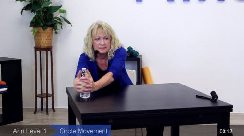 tabletop range of motion exercise with water bottle demonstrated by physical therapist