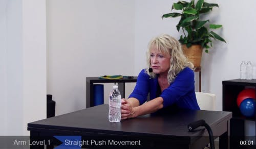 occupational therapist sliding water bottle across table for passive rom exercises