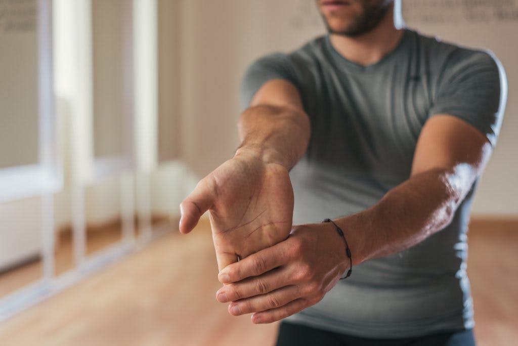 Man stretching fingers to relieve dystonia after brain injury