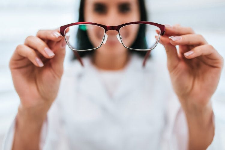 woman holding up glasses to correct vision side effects after tbi