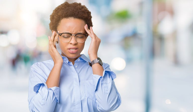 smart woman with glasses experiencing headache and rubbing temples