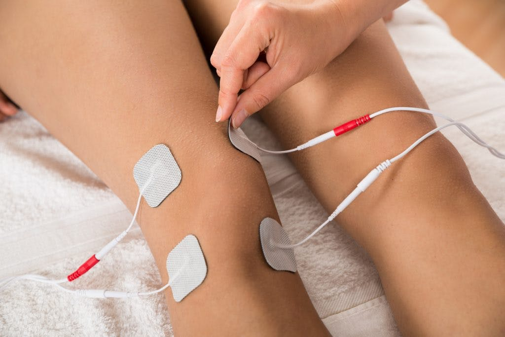 Therapist placing electrodes on patient's legs as part of their brain injury paralysis recovery