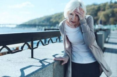 woman feeling pons stroke symptoms of dizziness