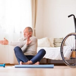 senior stroke patient sitting on yoga mat doing physical therapy stretches with arm