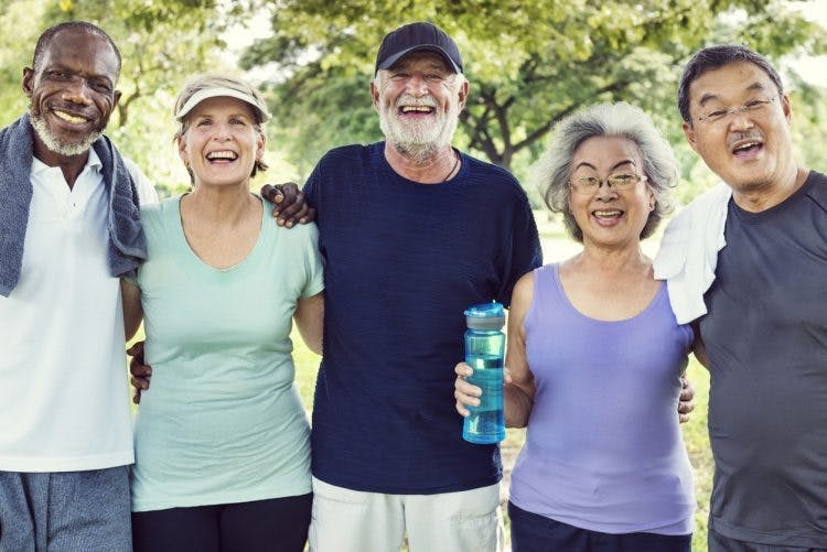 smiling senior friends with arms around each other after exercising with massed practice