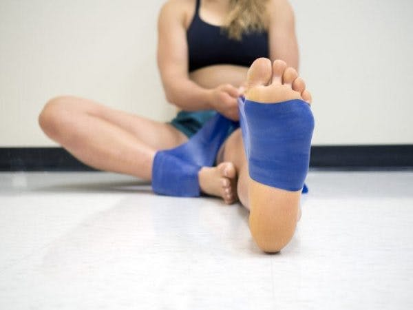 woman using resistance band around foot during physical therapy