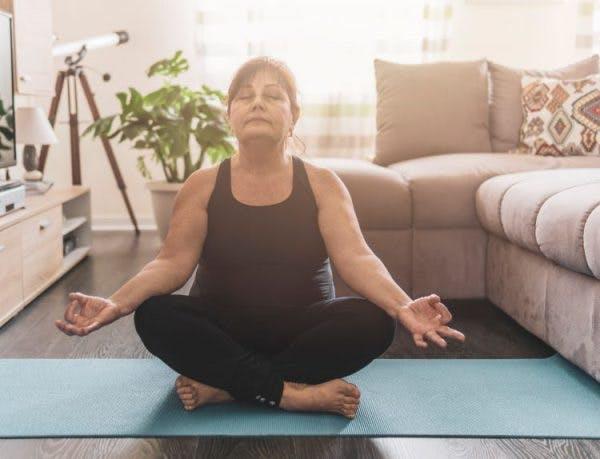 senior stroke survivor doing meditation on a yoga mat to practice mindfulness