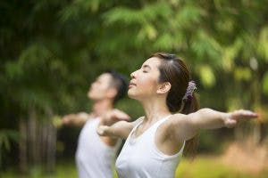 woman practicing balance in park to eliminate her dizziness after head injury