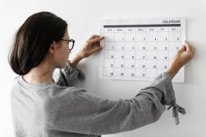Woman hanging up a calendar to help get her life back on track after brain injury