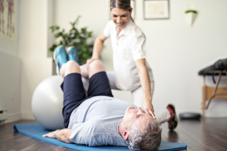 Therapist helping stroke patient with passive exercise as part of his stroke paralysis treatment