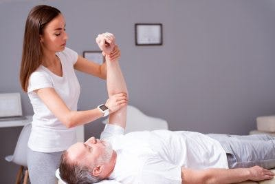 man stretching arm with physical therapist to relieve muscular effects of traumatic brain injury