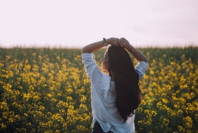 woman looking peaceful in a flower field practicing cognitive rest for concussion recovery