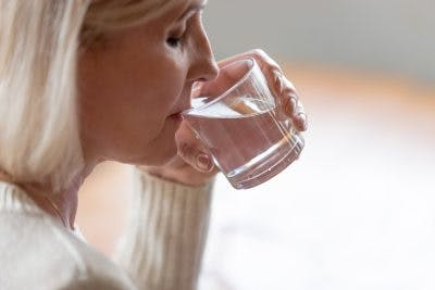woman drinking glass of water slowly because she has dysphagia after head injury