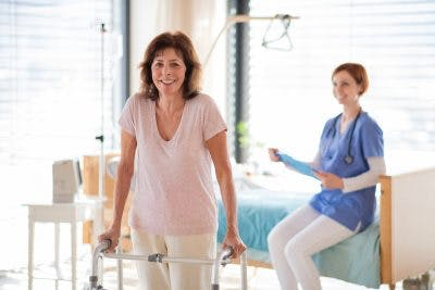 woman smiling and learning to walk with walker, her doctor is in the background also smiling