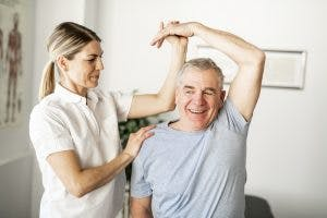Therapist performing passive range of motion exercises on patient to aid his brain injury paralysis recovery