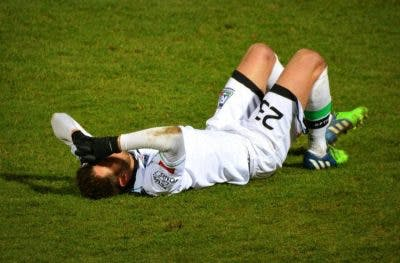 soccer player lying on grass holding his head because he has a concussion