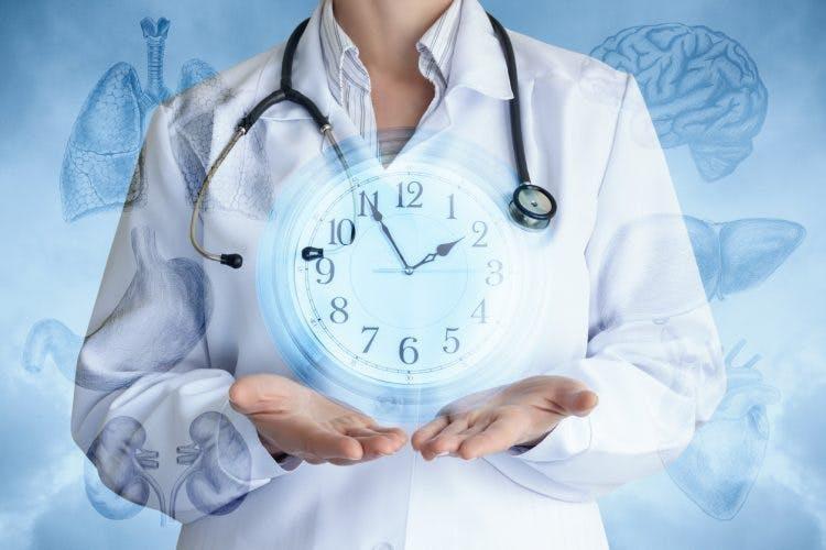 Doctor sosteniendo el reloj que muestra la línea de tiempo de recuperación de un acv