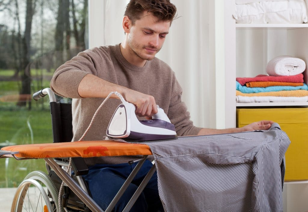 man in wheelchair ironing shirt on ironing board