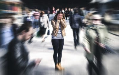 Woman having a brain injury sensory overload in public place