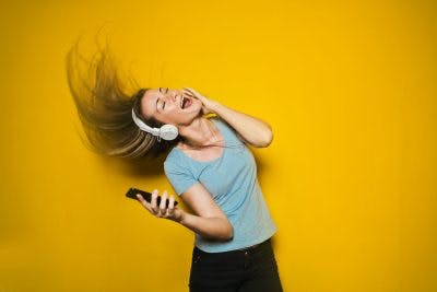 woman swinging her hair and listening to music in front of yellow background