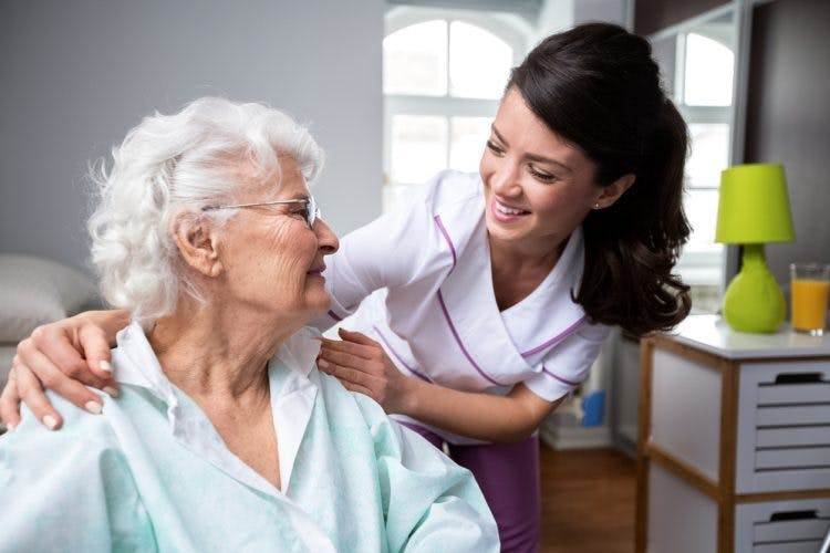 nurse helping elderly woman with spinal cord injury initiate bowel program