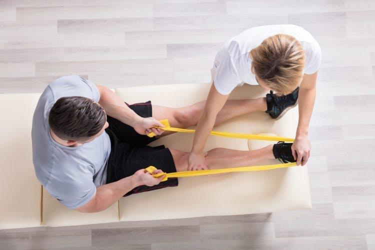 Hombre haciendo ejercicios para las piernas después de un acv con un terapeuta.