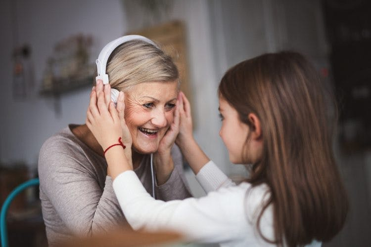 little girl helping her grandmother put on headphones to listen to music
