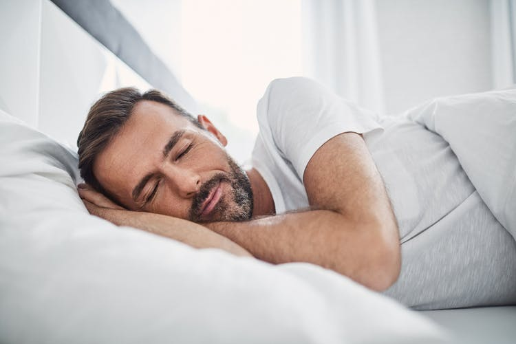middle aged man sleeping after head injury with hands under head