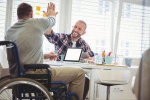 Man giving high-five to person in wheelchair