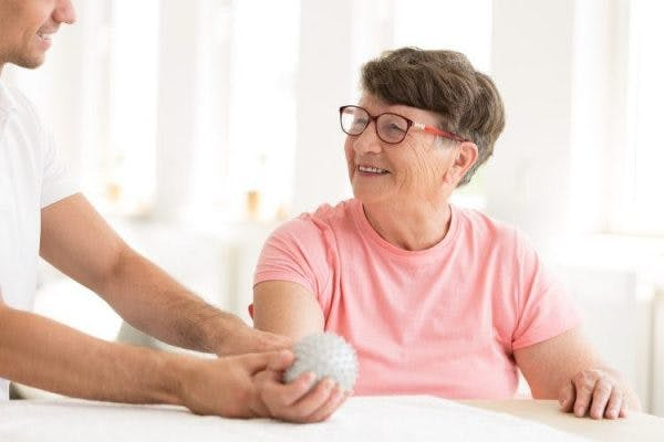 physiotherapist helping survivor with hand spasticity treatment by stretching hand with ball