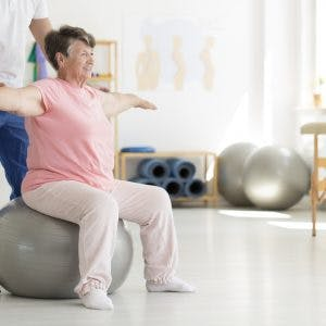 senior exercising on exercise ball because she has balance problems after cerebellum brain damage