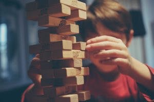 boy playing jenga, another one of the best games for brain injury