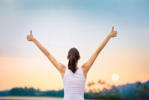 Young woman with arms in the air giving thumbs up and celebrating a small victory