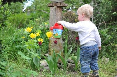 child with cerebral palsy watering flower to practice wrist control