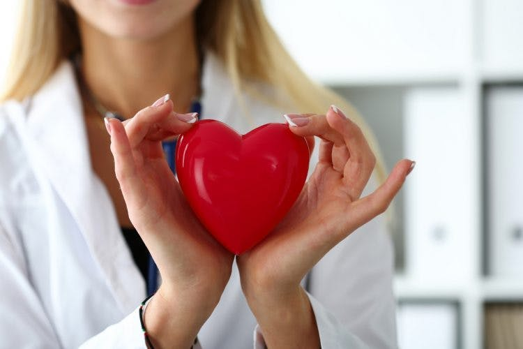 doctor holding a red heart between her hands to symbolize hand recovery