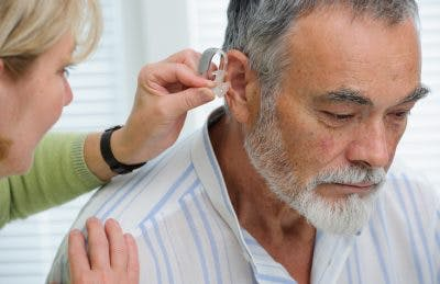 Doctor inserting hearing aid in brain injury patients ear to help with hearing loss