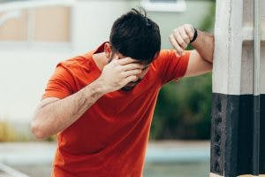 man leaning on wall because he has dizziness and loss of balance, symptoms of cerebellum brain damage
