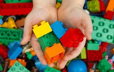 kid with cerebral palsy playing with legos to develop strength in fingers