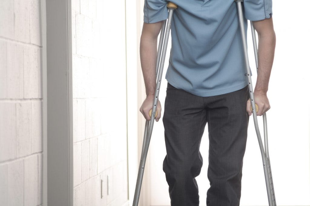 Close up of man walking with crutches
