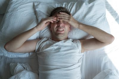 Man lying in bed suffering from a migraine after TBI