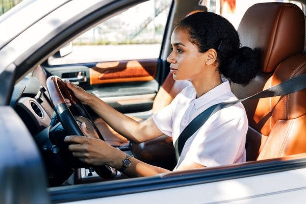 capable brain injury survivor sitting behind the wheel about to take a driving test