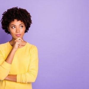 woman standing in front of purple background with a thinking face to symbolize memory problems after brain injury