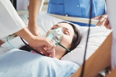 Doctor putting oxygen mask on patient experiencing storming after brain injury