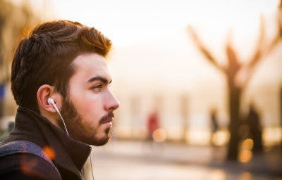 man listening to music through headphones while sitting on park bench